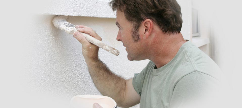 An image showing an A&J Painters professional painting contractor painting an exterior wall white
