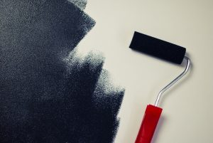an image of a roller paintbrush painting black paint onto a white wall