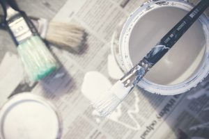 An image of open paint pots on pieces of newspaper, surrounded by used paint brushes that have been used to make home improvements.