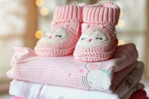 An image of a pile of baby clothes in pink.