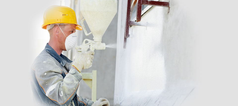 An image showing an A&J Painters decorator using a spray paint gun to paint a room.