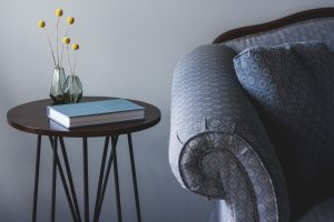 An image showing a close up of a grey patterned sofa next to a small round side table with books and a vase of fresh flowers on top.