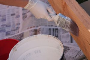 An image of a painter pating a home to improve its appearance.
