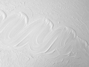 An image of white paint on a ceiling which shows patches on uneven paint.