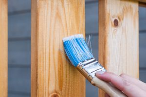An image of a skilled painter and decorator varnishing wood to protect it.