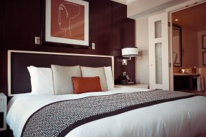 An image of a bedroom with a dark coloured statement wall and light woodwork.