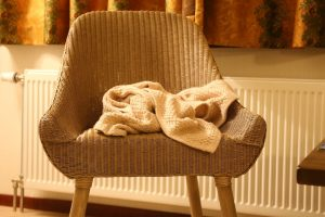 An image of a cosy bedroom with a decorative chair with a blanket laying over it.