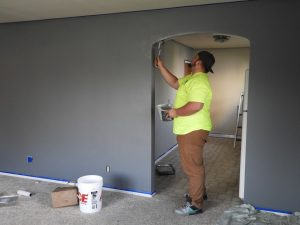 An image of a professional decorator painting a living room.